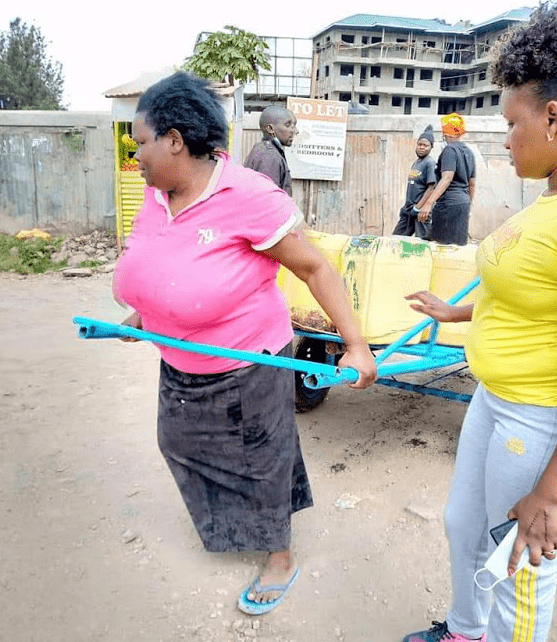 woman pictured pulling a loaded 'Mkokoteni' gets help from well-wishers